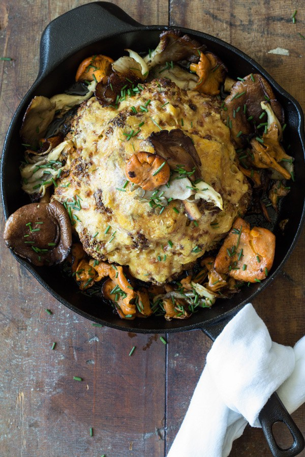 Top view of Whole Roasted Cauliflower with Wild Mushrooms in a skillet.