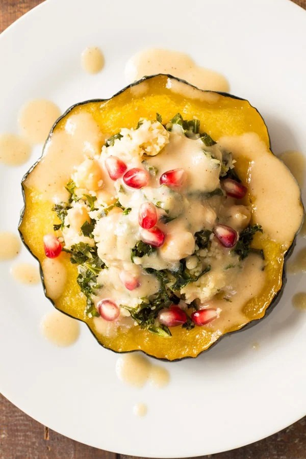 Top view of Bulgur Stuffed Acorn Squash with sauce and pomegranate seeds.