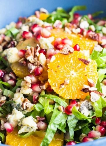 Close up of the best winter salad - Romaine Lettuce, Orange Slices, Chopped Pecans, Blue Cheese and Pomegranate Seeds.