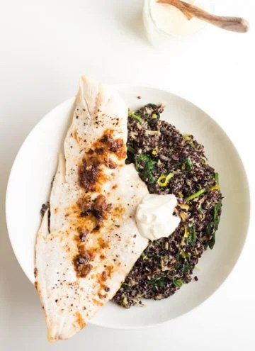 Top view of Haddock with Black Quinoa Risotto and creme fraiche on a white plate, and a cup with creme fraiche with a wooden spoon.