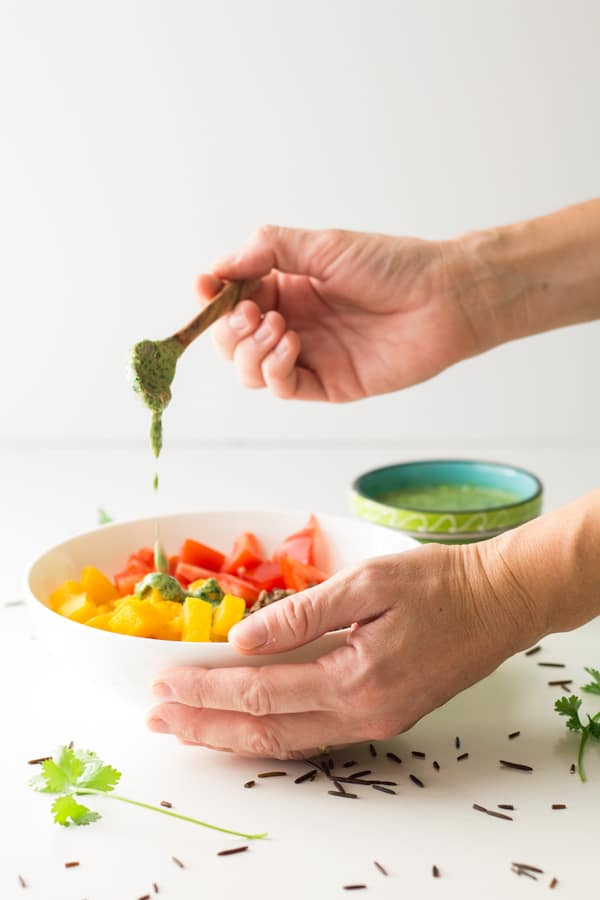 Hand pouring Out of This World Tahini Herb Sauce over a bowl of Warm Vegan Wild Rice Salad.
