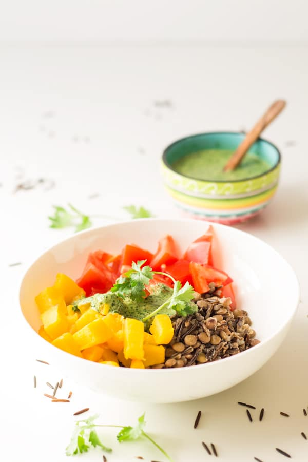 Healthy Warm Vegan Wild Rice Salad in a white bowl and a cup of Out of This World Tahini Herb Sauce in the back.