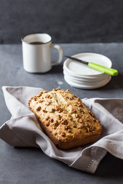 Freshly baked Banana Bread with Maple Candied Walnuts on a beige napkin, a cup of coffee, and some serving plates with a knife.