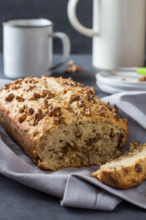 Close up of sliced Banana Bread with Maple Candied Walnuts, and a cup of coffee.
