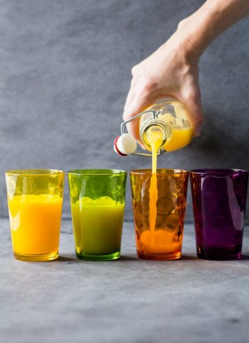 Hand pouring Immune Booster Juice from a bottle into four colored drinking glasses.