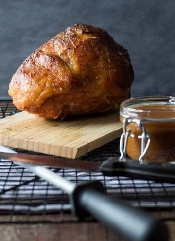 Baked Maple Mustard Ham on a wooden board and a jar of gravy.