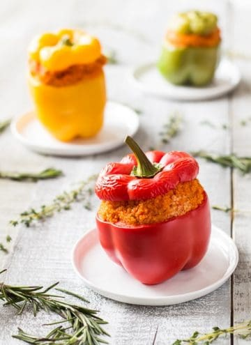 Close up of red Bulgur Stuffed Bell Pepper on a plate. Yellow and green peppers in the background.