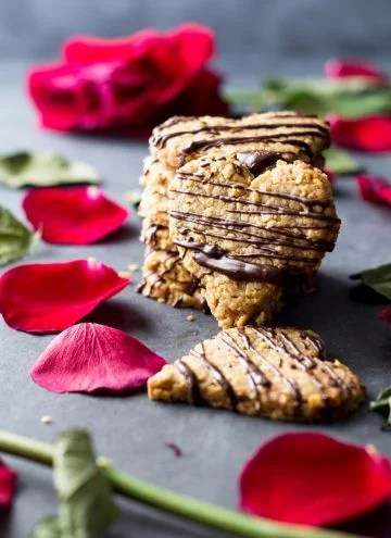 Heart-shaped spelt cookies stacked on the counter with rose petals.