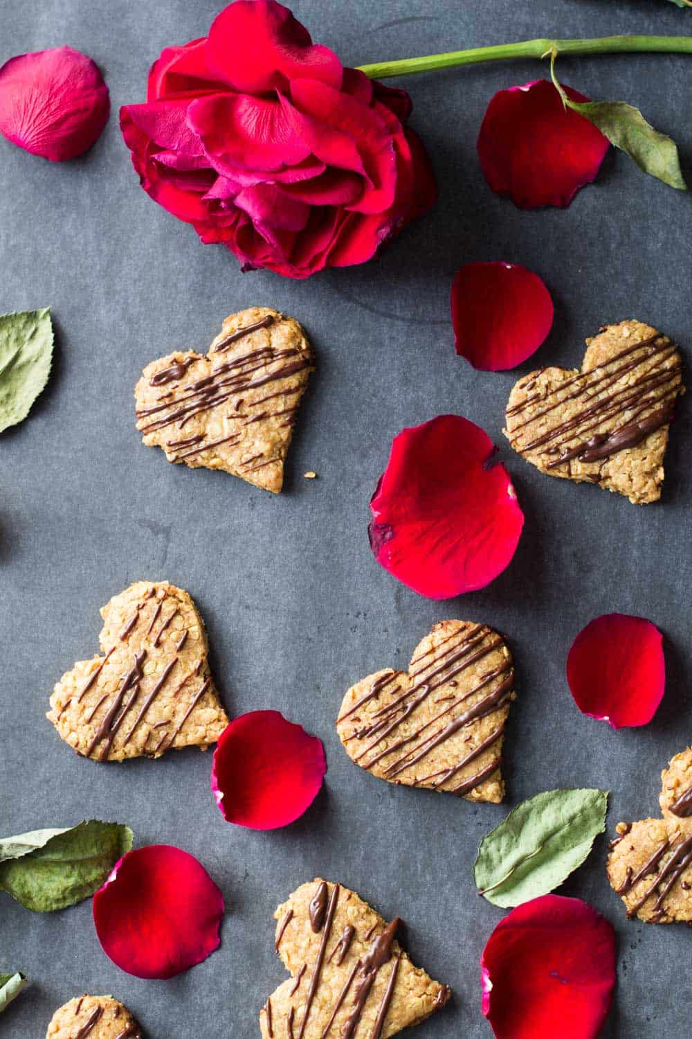 Heart-shaped spelt cookies spread on the counter with a rose and rose petals.
