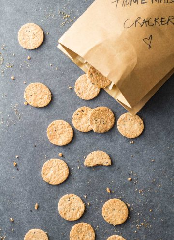 Top view of Homemade Crackers scattered on the counter from a paper bag.