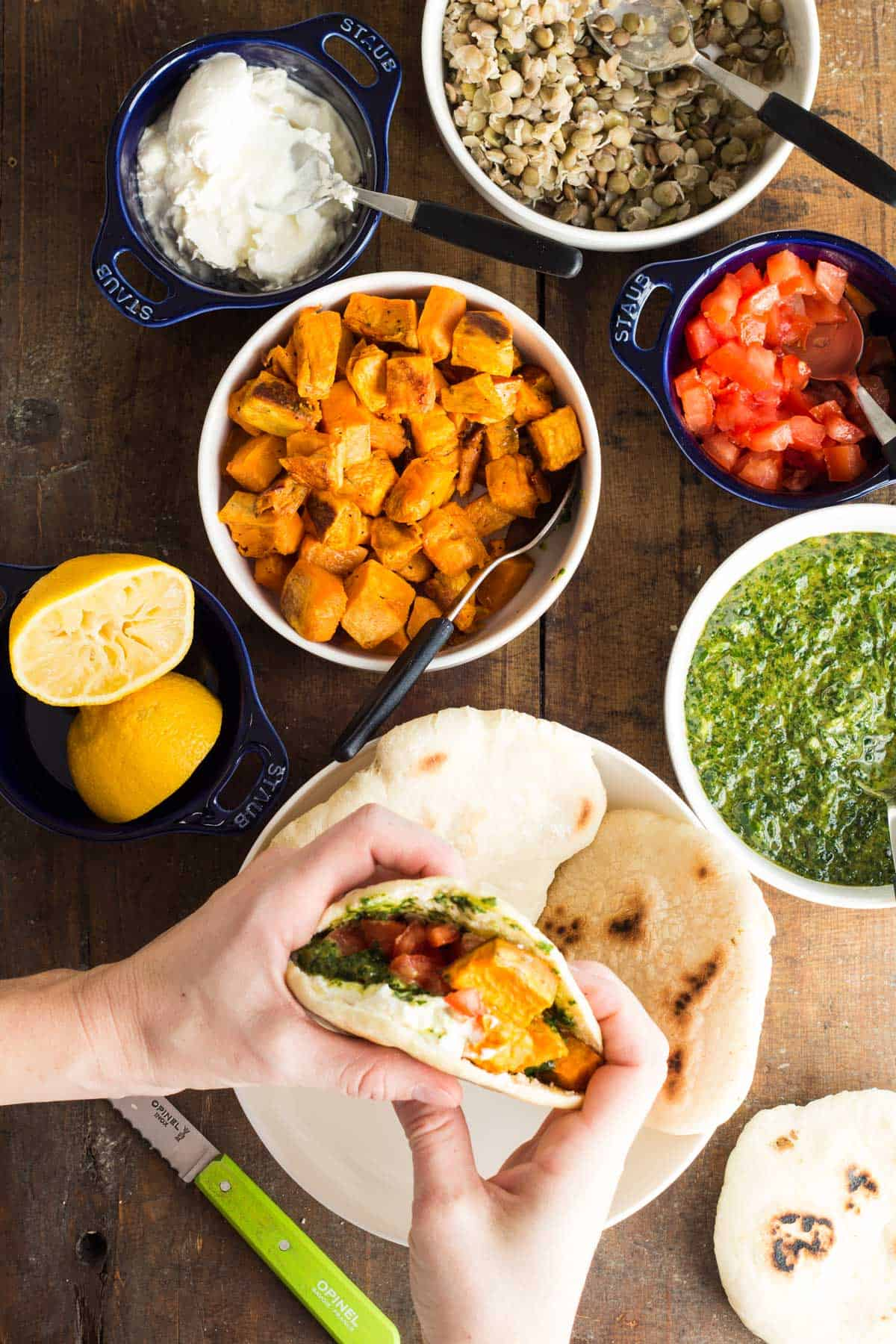 Hands holding a Pita With Sweet Potato Lentil Filling and Out of This World Tahini Herb Sauce, and all the ingredients in bowls.