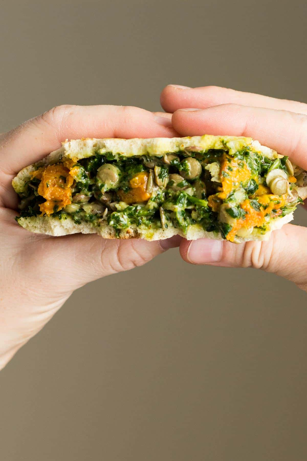 Close up of hands holding Pita With Sweet Potato Lentil Filling and Out of This World Tahini Herb Sauce to show texture.