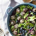 Warm Goat Cheese Salad in blue salad bowl with blueberries
