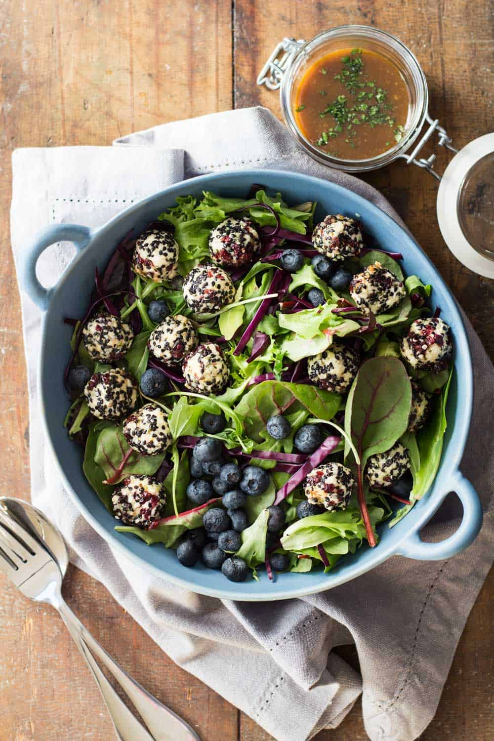 Warm Goat Cheese Salad in blue salad bowl on wooden table