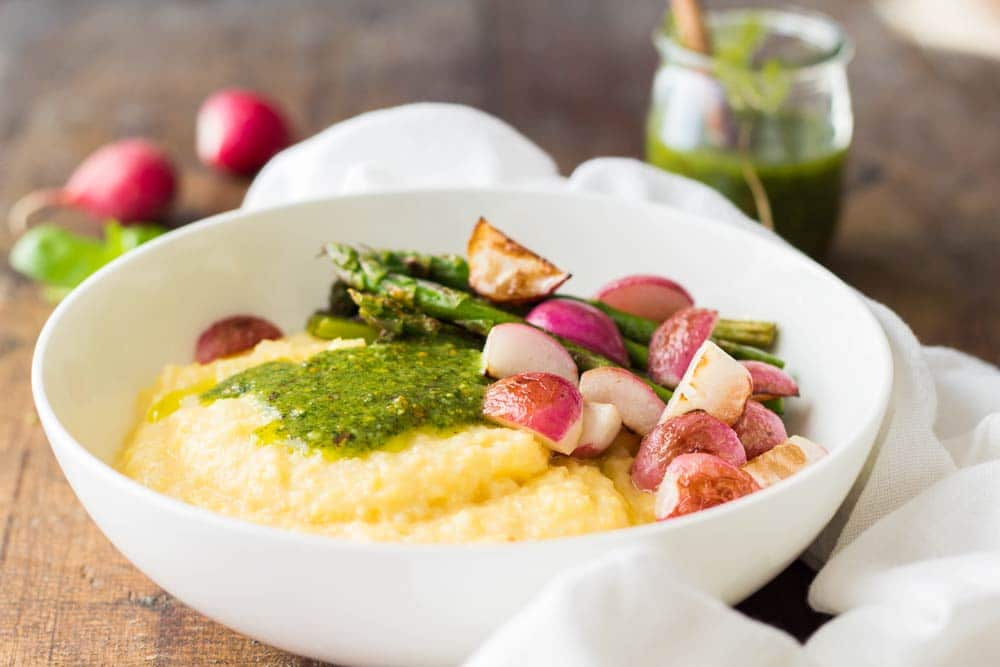 Creamy Parmesan Polenta with Grilled Vegetables and 5-Minute Basil Pistachio Pesto in a white bowl, and an open jar of pesto sauce in the background.