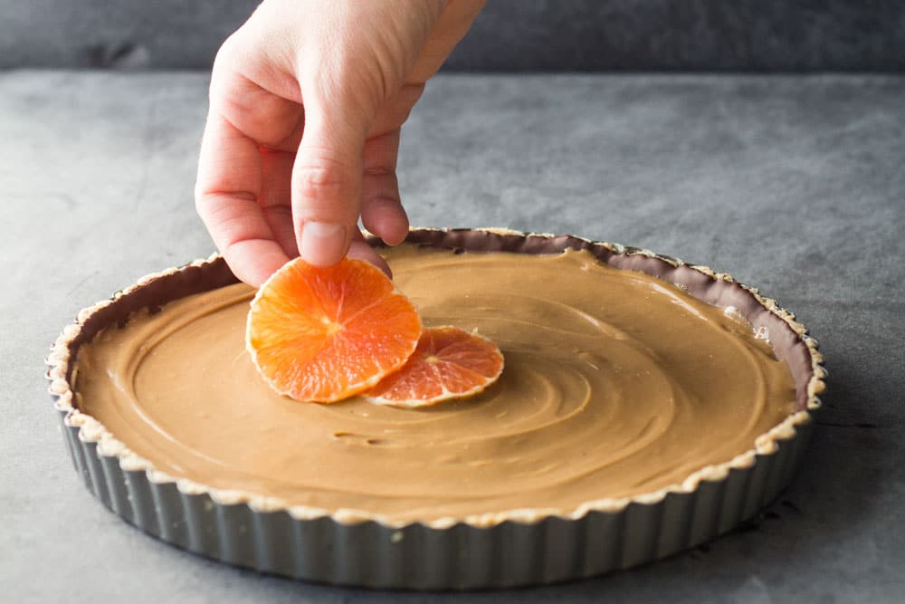 placing oranges into a chocolate orange tart