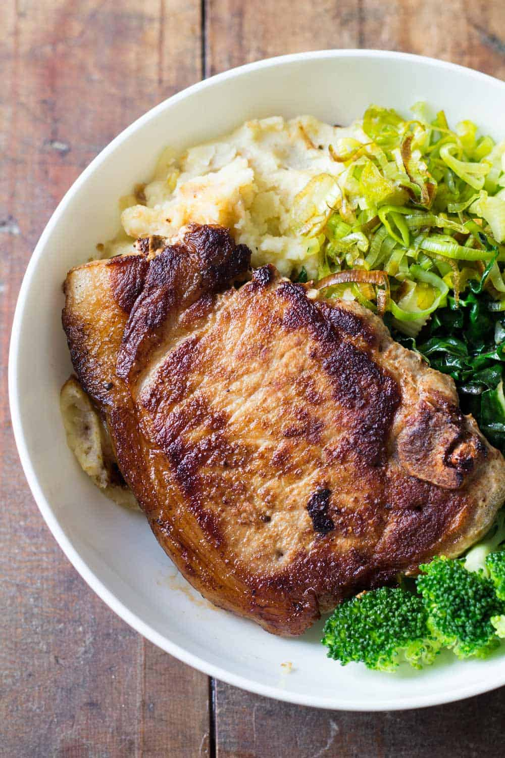 Perfect Pork Chops on mashed potatoes and vegetables