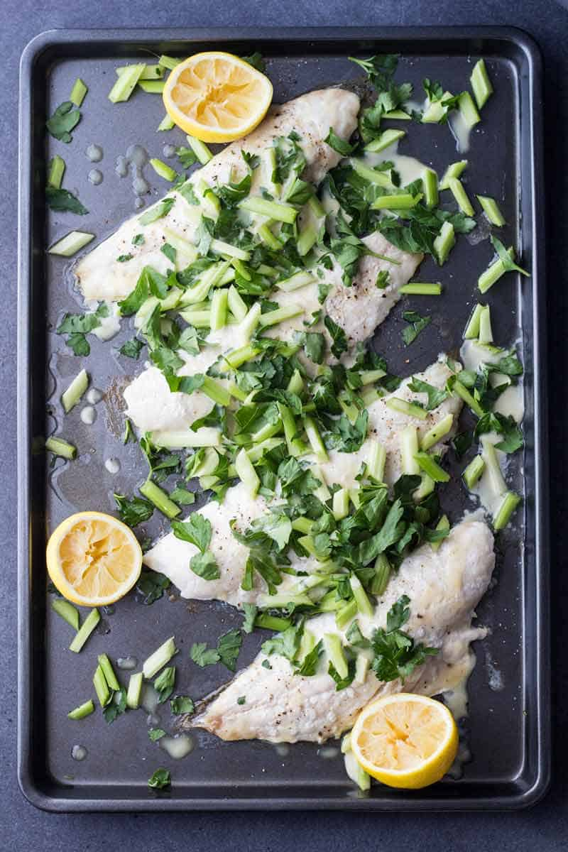 Top view of Snapper Fillet With Celery Parsley Salad on a baking sheet with sliced lemons.