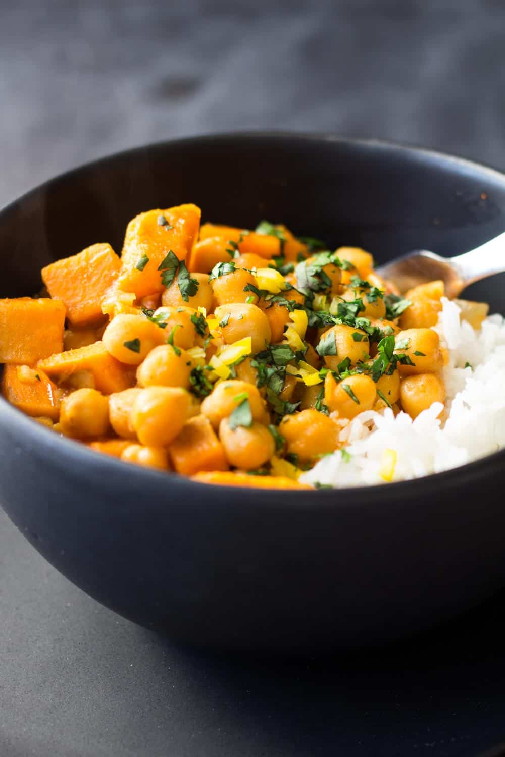 Sweet Potato Chickpea Curry in black bowl served with rice