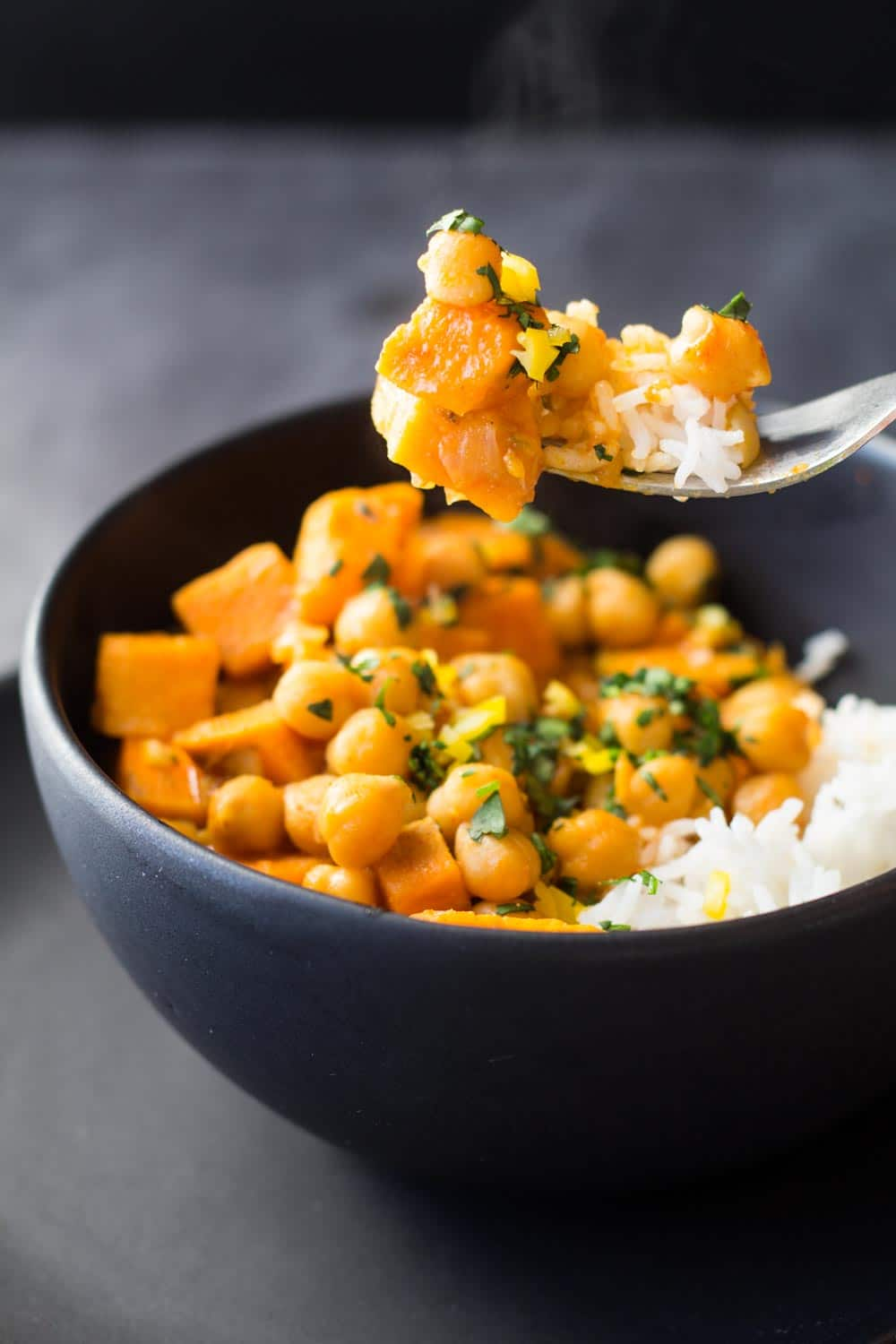 Vegan Chickpea Curry on fork over black bowl