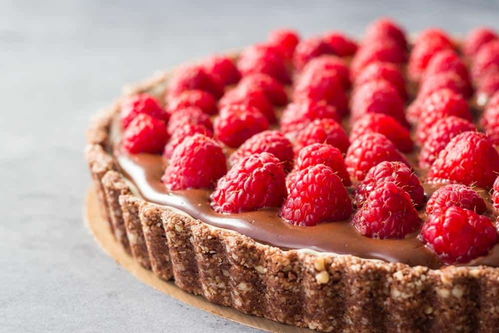 Close up of chocolate raspberry tart with almond crust showing creaminess of coconut cream chocolate filling.