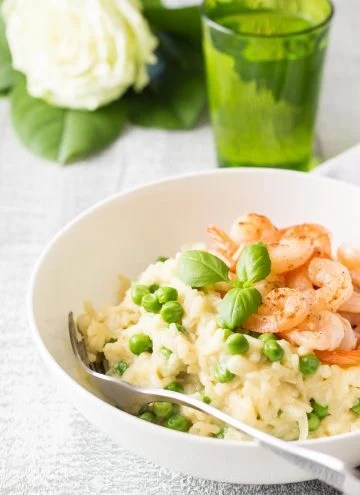 Shrimp and Pea Risotto on a white plate with a fork, a glass of water and a flower.