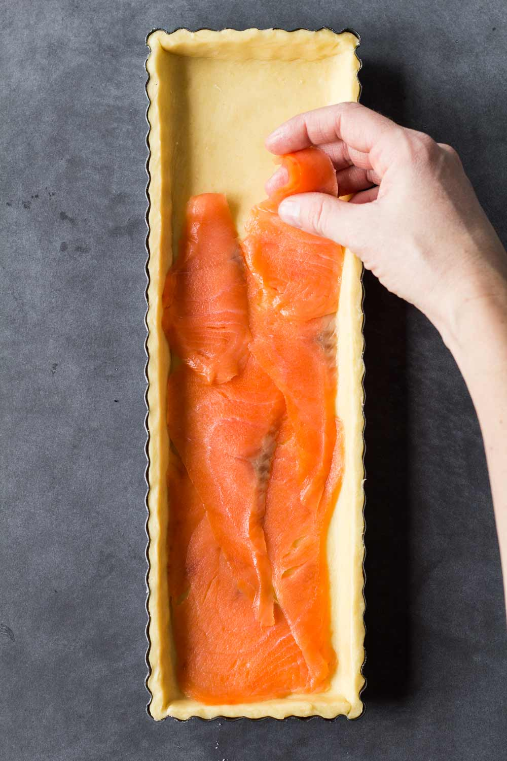 placing slices of smoked salmon into a puff pastry crust
