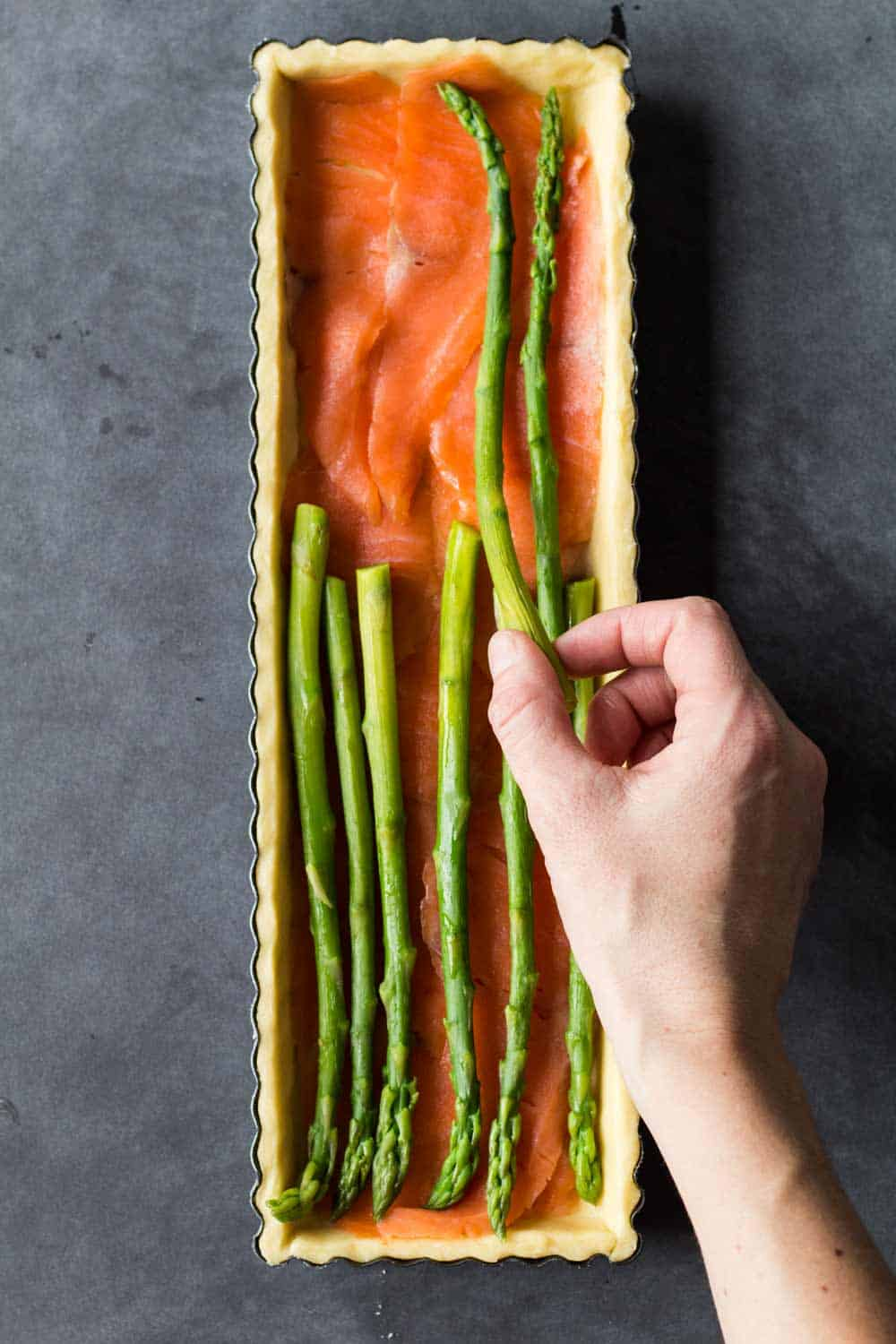 assembling smoked salmon and asparagus quiche