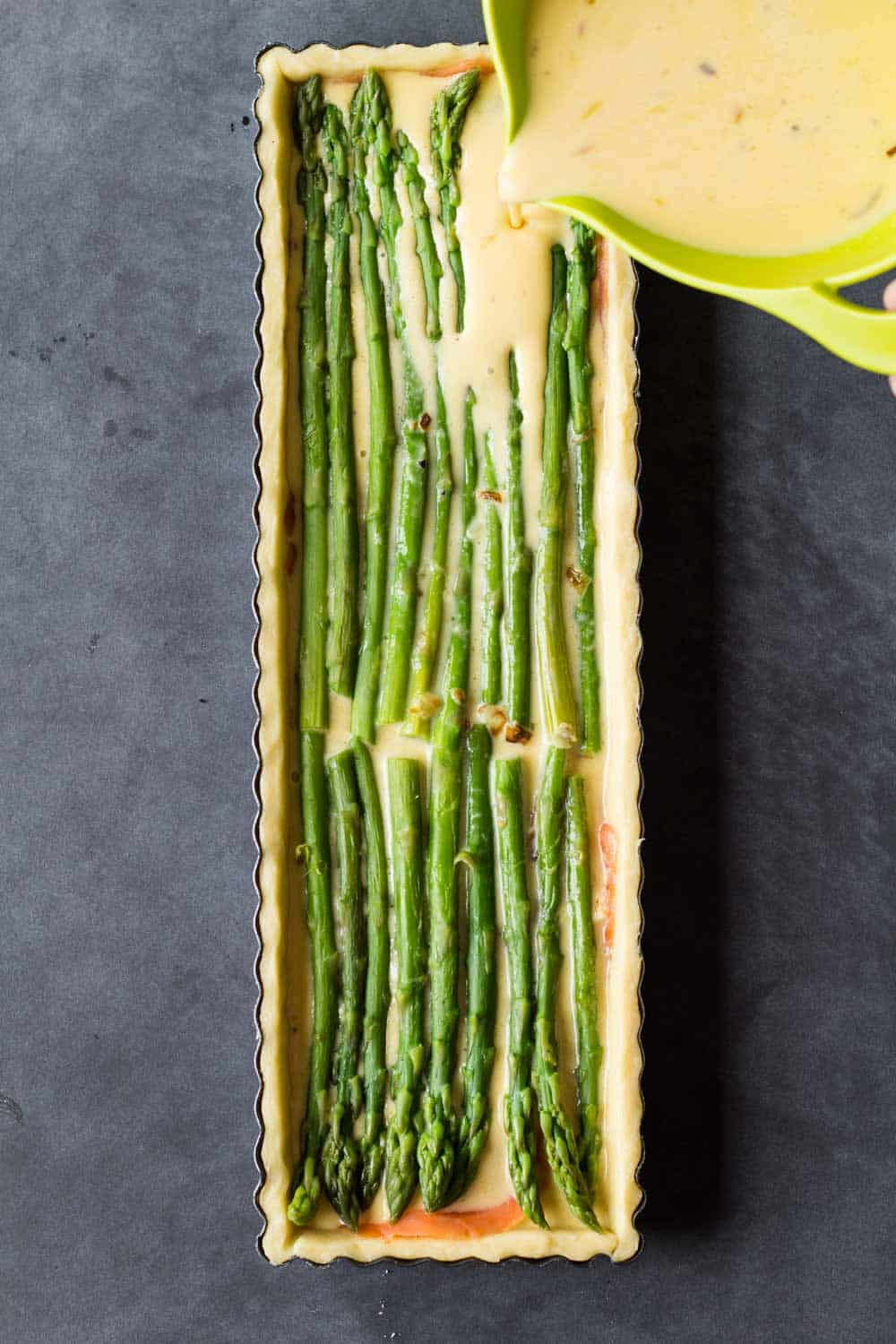 pouring egg batter into a tart pan over asparagus spears to make quiche