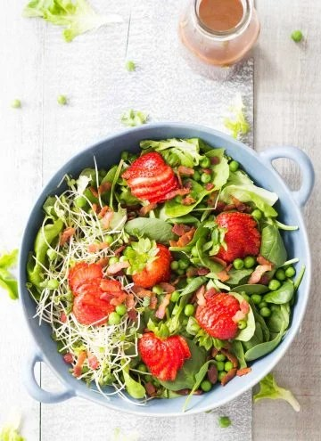 Top view of Strawberry Bacon Spring Salad and a jar of Maple Mustard Balsamic Dressing.