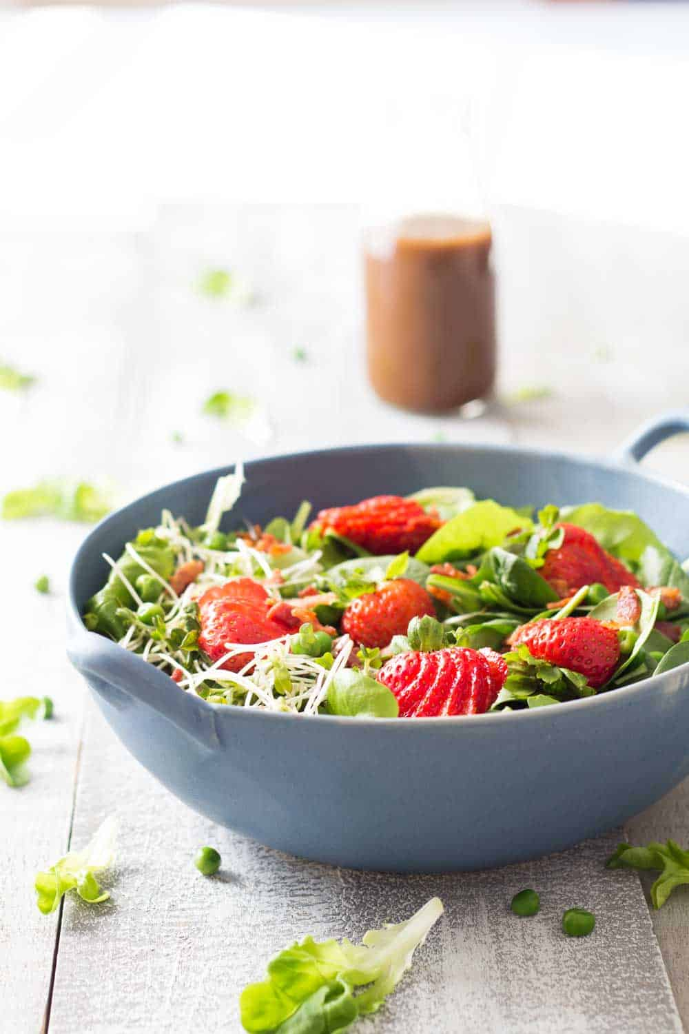 Strawberry Bacon Spring Salad in a blue bowl, and a Maple Mustard Balsamic Dressing.