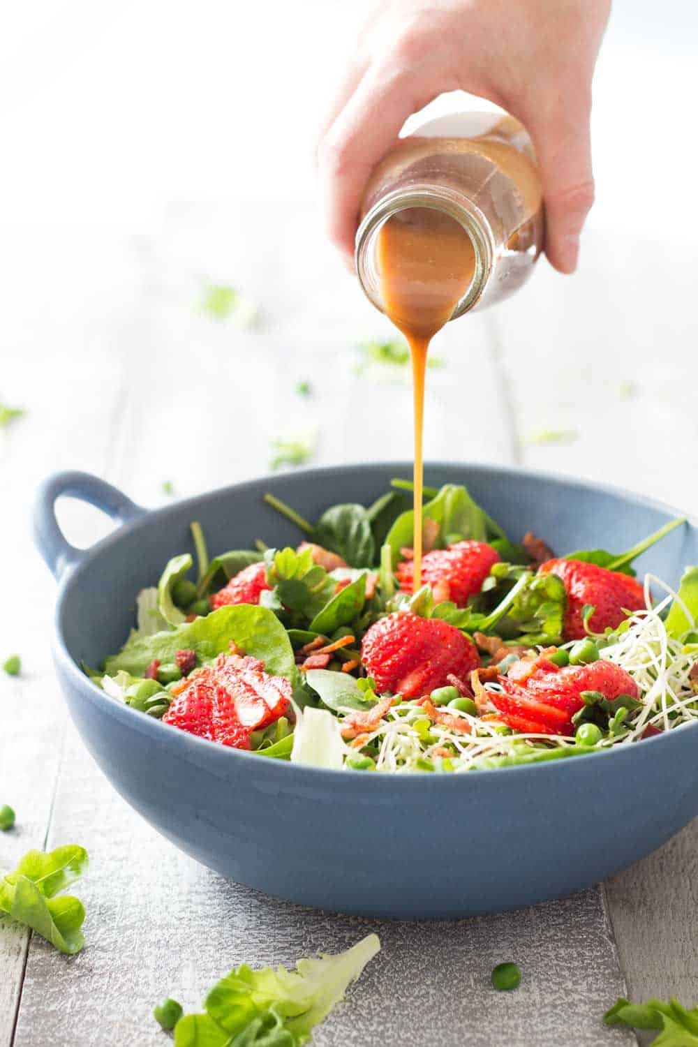 Hand pouring Maple Mustard Balsamic Dressing over Strawberry Bacon Spring Salad in a blue bowl.