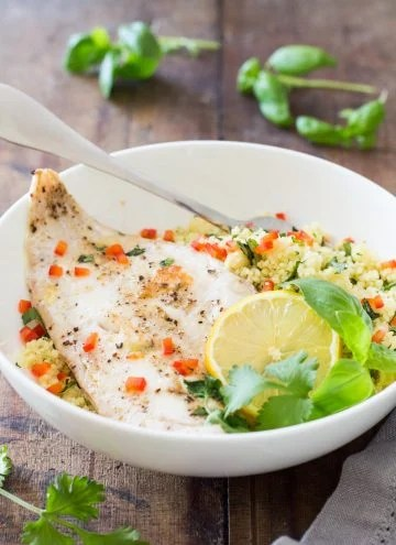Plate of Baked Haddock with Herb Couscous garnished with fresh herbs, a slice of lemon and a fork.