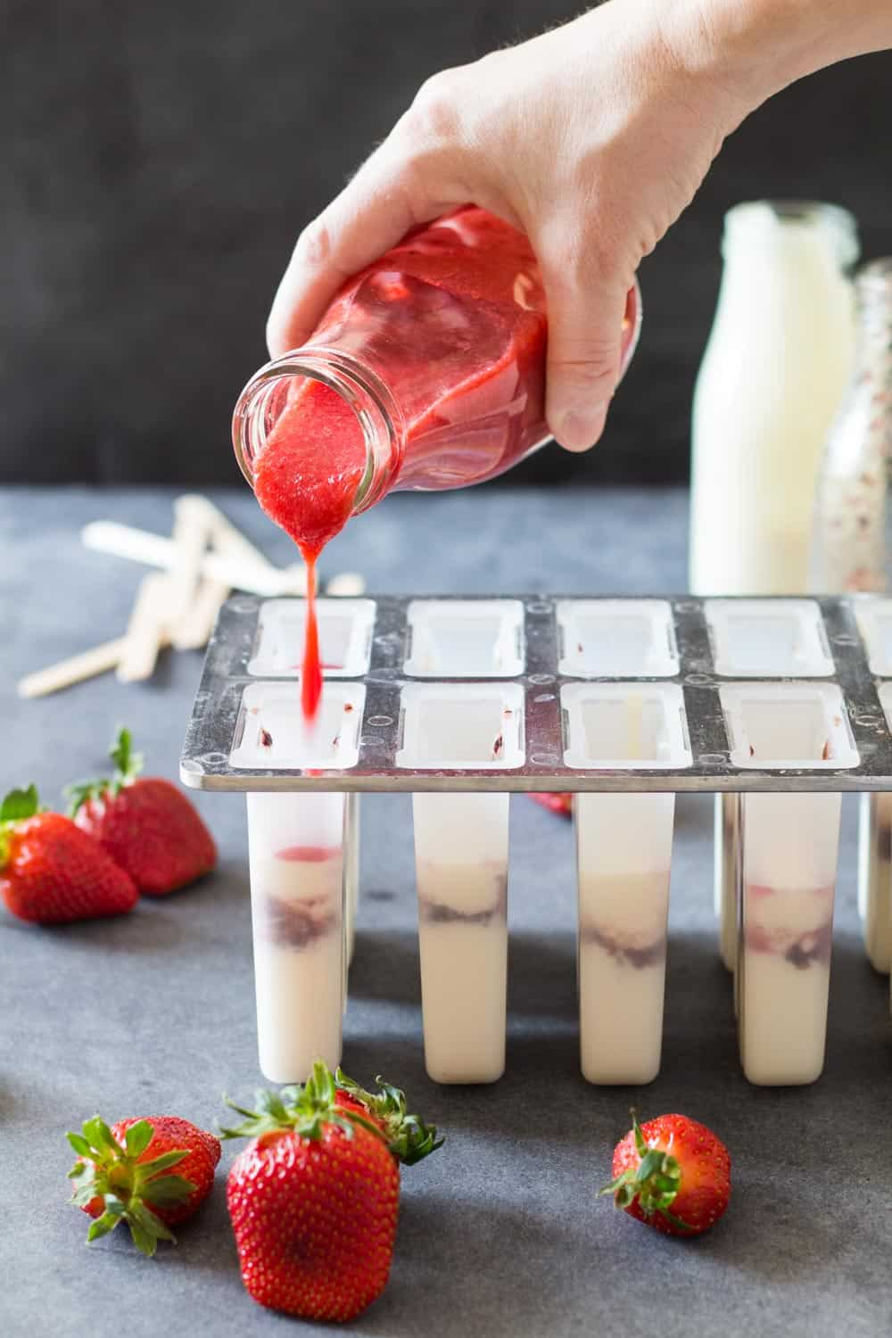 Hand pouring strawberry mix into popsicle molds containing greek yogurt and blueberry mix.