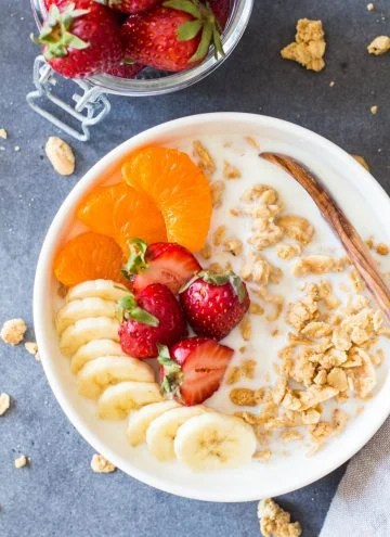 Bowl of Peanut Butter Granola with fruit and milk, and a wooden spoon.