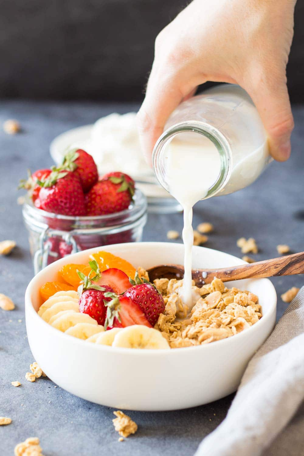 Pouring milk over peanut butter granola and fruit in a bowl
