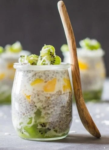 Close up of jar of Tropical Chia Pudding with a wooden spoon.