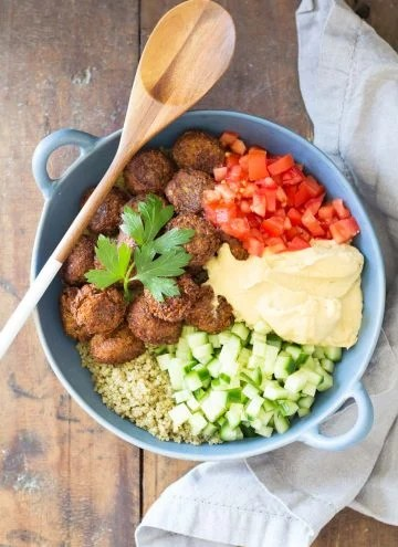 Top view of Vegan Quinoa Falafel Bowl garnished with fresh parsley, and a wooden spoon.