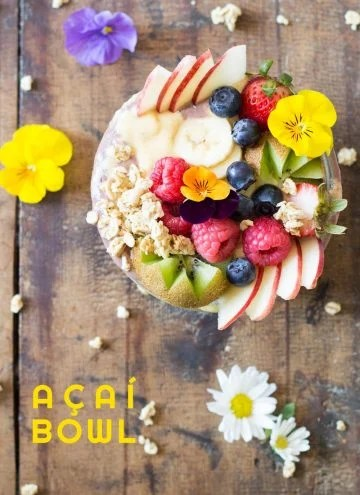 Top view of Acai Bowl topped with fresh fruit and flowers, on a rustic wood table with flowers, and text overlay.