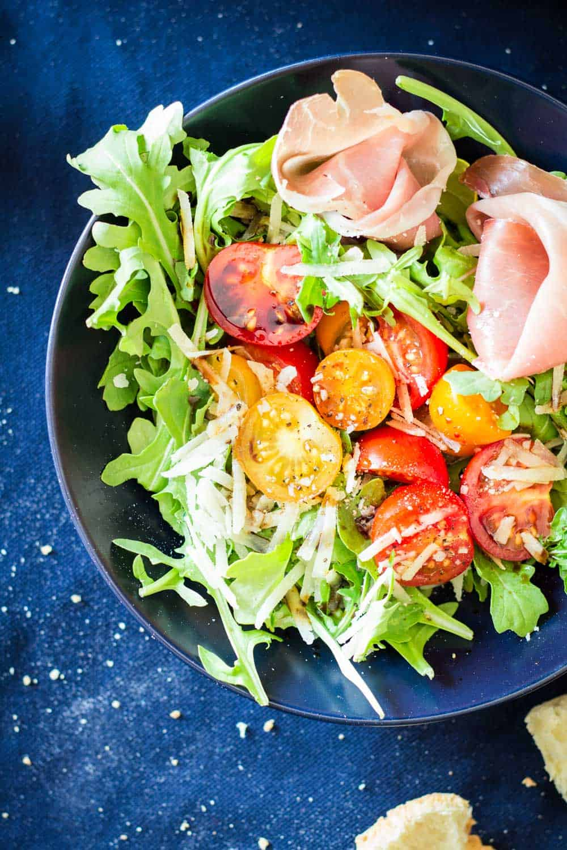 Top view of Arugula Tomato Prosciutto Salad in a blue bowl.