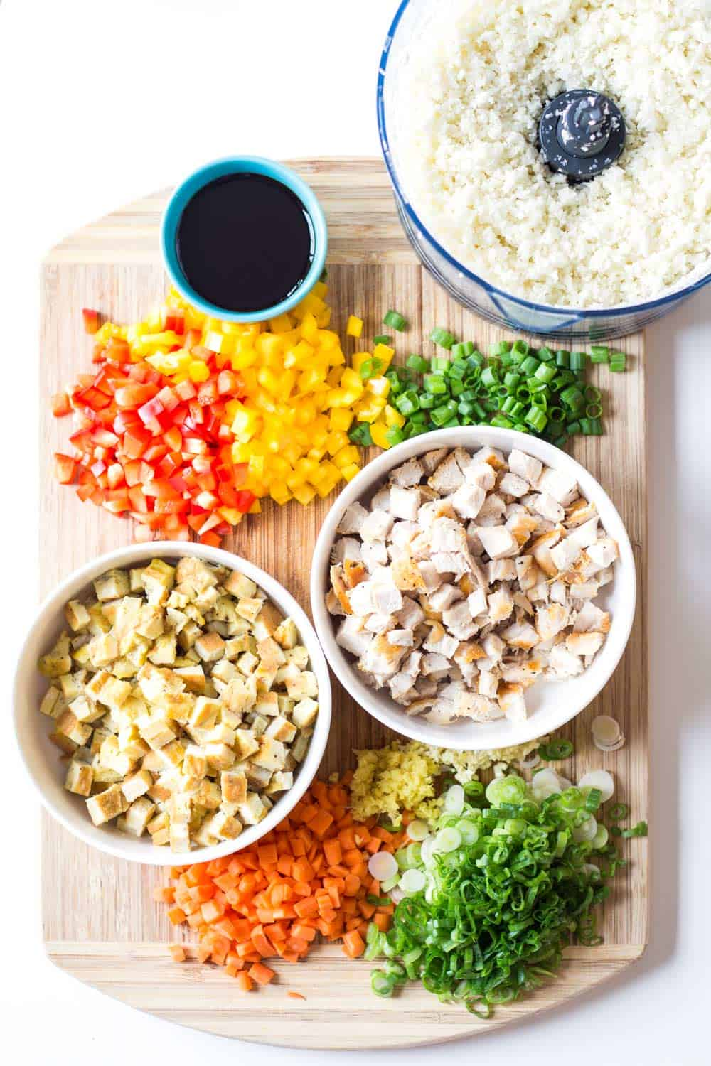 Fresh chopped ingredients for Cauliflower Fried Rice laid out on a chopping board.