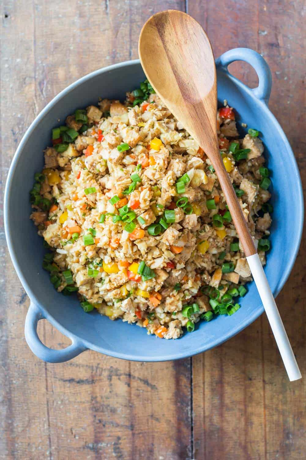 Top view of Cauliflower Fried Rice in a blue bowl with a wooden spoon.