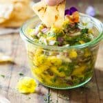 Hand dipping a tortilla chip in a Mango Salsa jar.