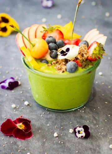 Green Smoothie Bowl topped with fresh fruit and fresh flowers.