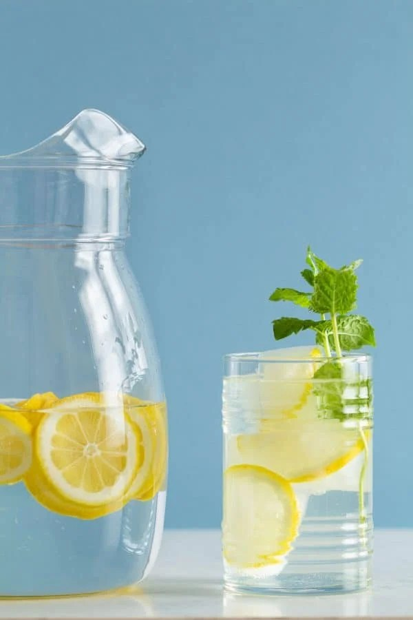 Pitcher with water and lemon slices and glass with ice and lemon slices