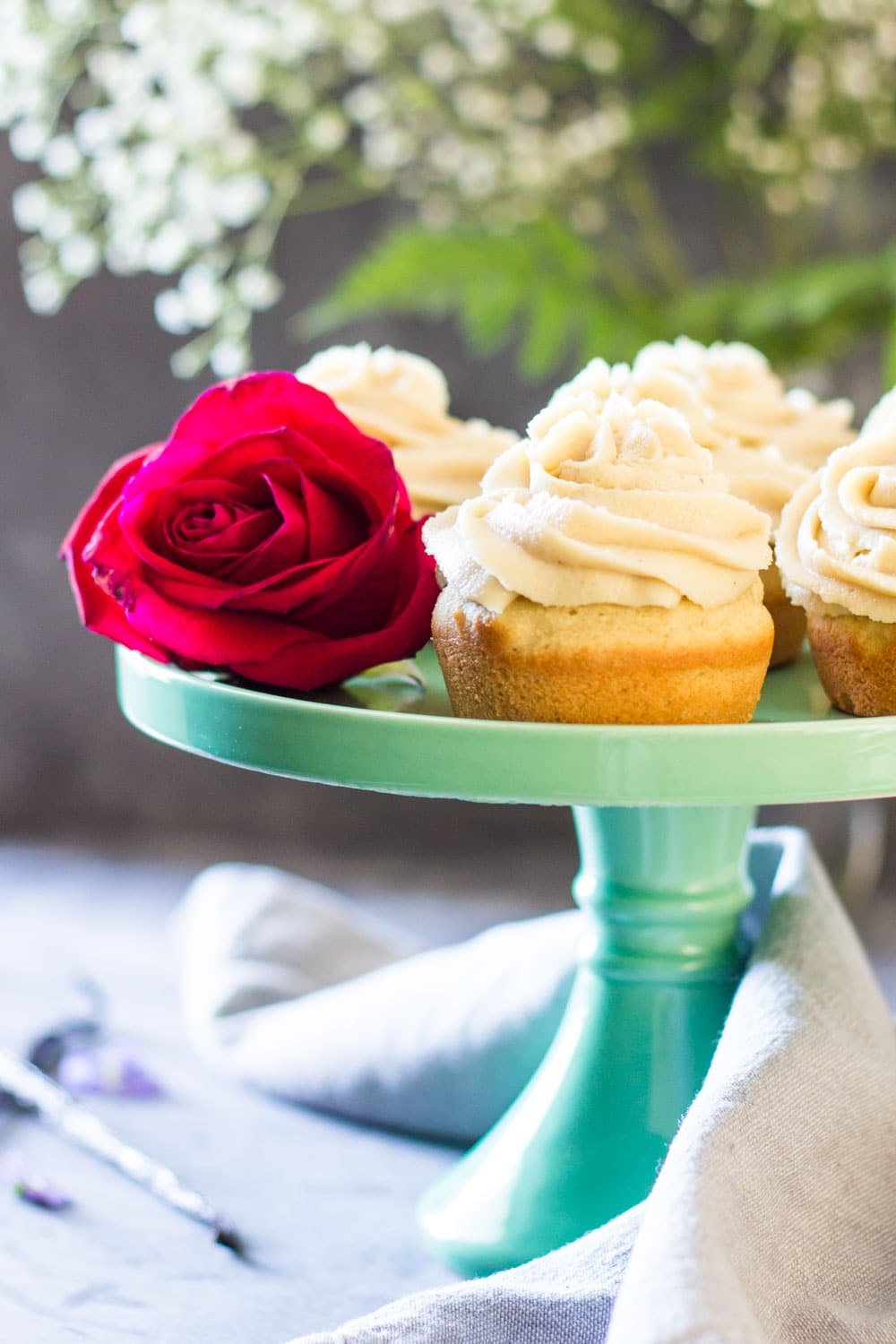 Moist Vanilla Cupcakes on a green cake stand with a rose.