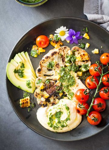 Top view of Grilled Cauliflower Steak with chimichurri sauce, cherry tomatoes and avocado on a black plate.