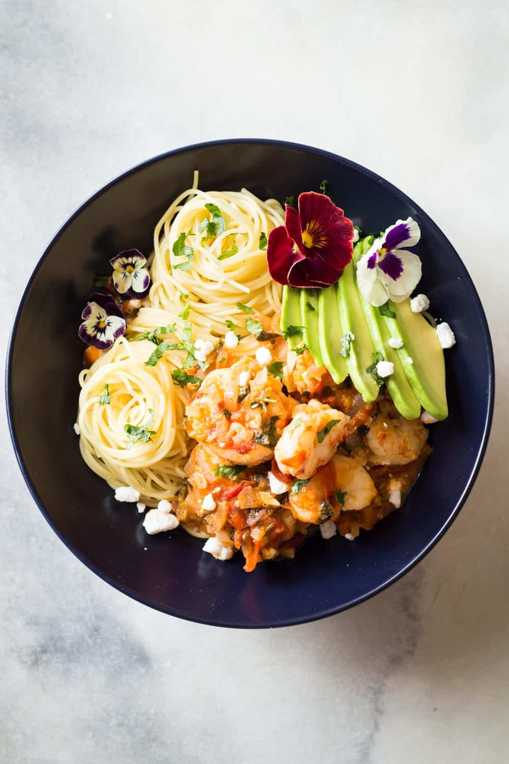 Top view of Mexican-Style Shrimp Capellini Pasta in a black bowl decorated with fresh flowers.