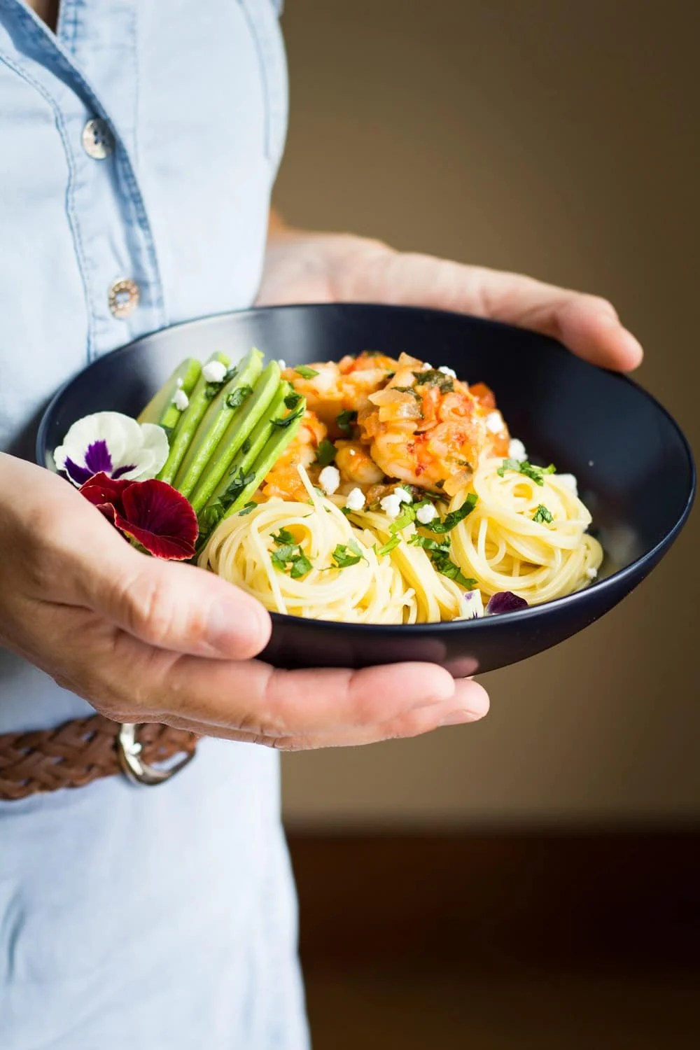 Person holding a bowl of Mexican-Style Shrimp Capellini Pasta.