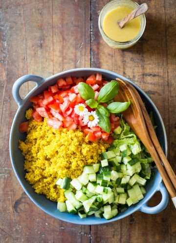 Turmeric Quinoa Salad in a blue bowl with wooden salad spoon and fork, and a jar of honey mustard dressing with a wooden spoon.